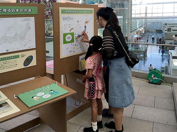 空港ターミナルでモバイルミュージアムのパネルにシールを貼る親子